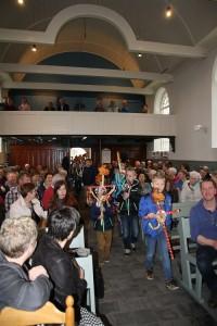 De gemeenteleden verwelkomen de kinderen in de kerk